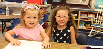 Two students in a classroom at the summer program.